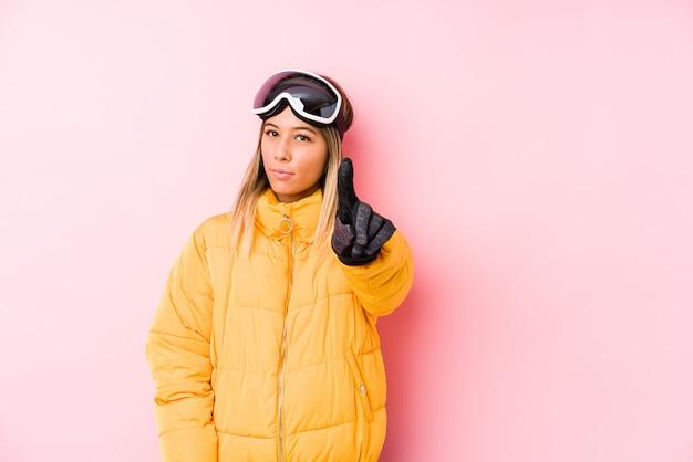 La giovane donna caucasica che indossa uno sci copre di uno sfondo rosa che mostra il numero uno con il dito. Foto Premium