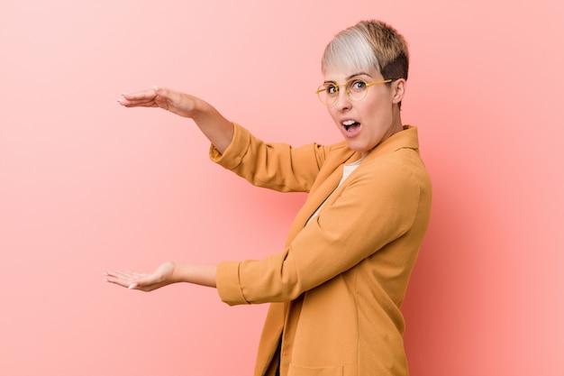 La giovane donna caucasica che porta i vestiti casuali di affari ha colpito e stupito tenendo un copyspace fra le mani. Foto Premium