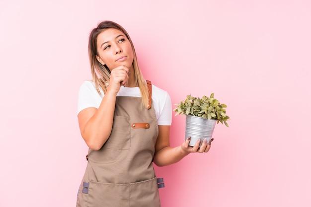 La giovane donna caucasica del giardiniere ha isolato lo sguardo lateralmente con l'espressione dubbiosa e scettica. Foto Premium