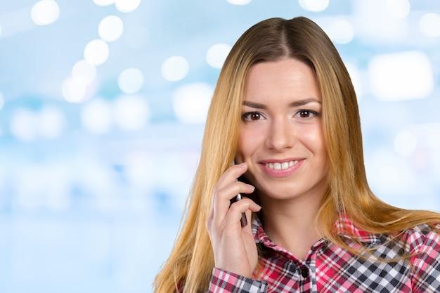 La giovane donna caucasica felice sta chiamando con un telefono cellulare Foto Premium