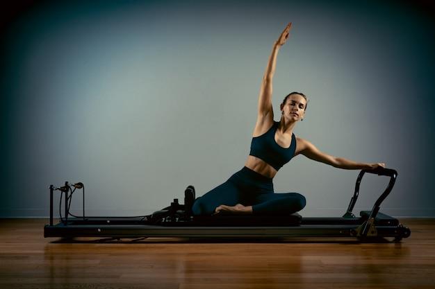 La giovane donna che fa i pilates si esercita con un letto del riformatore. bellissimo istruttore di fitness sottile Foto Premium