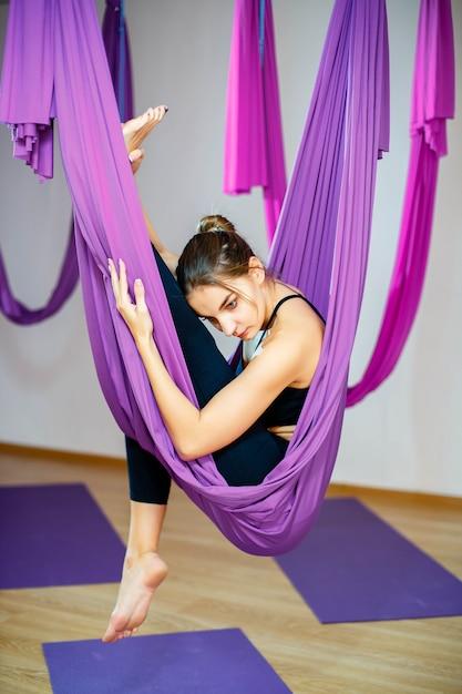 La giovane donna che fa l'allungamento si esercita facendo uso dell'amaca. yoga aerea Foto Premium