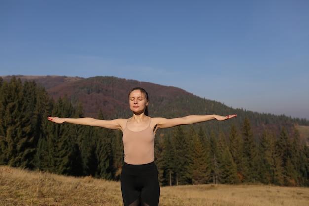 La giovane donna che fa l'allungamento si esercita sulla natura in montagne. posa di yoga di pratica della ragazza di sport in ghette. bellissimo paesaggio forestale Foto Premium