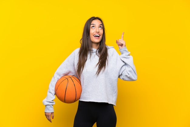 La giovane donna che gioca a pallacanestro sopra la parete gialla isolata che intende realizzare la soluzione mentre solleva un dito su Foto Premium