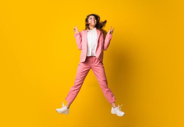La giovane donna che salta sopra la parete gialla isolata Foto Premium