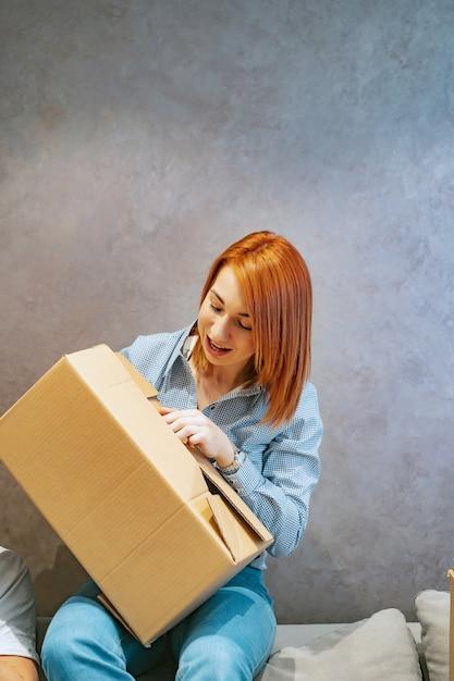 La giovane donna che tiene le scatole di cartone e la scuote Foto Gratuite