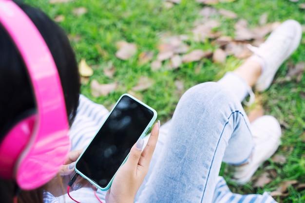 La giovane donna che usando la musica mobile e d'ascolto con le cuffie in giardino con si rilassa Foto Premium