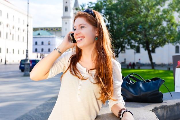 La giovane donna chiama con il telefono cellulare nel parco Foto Premium