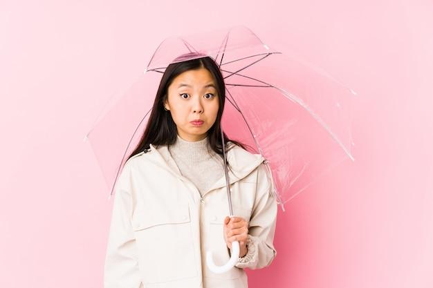 La giovane donna cinese che giudica un ombrello ha isolato le spalle di scrollate di spalle e gli occhi aperti confusi. Foto Premium