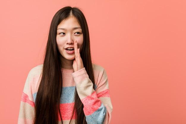 La giovane donna cinese fredda sta dicendo una notizia di frenata calda segreta e sta guardando da parte Foto Premium