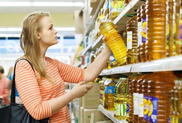 La giovane donna compra l'olio di girasole Foto Premium