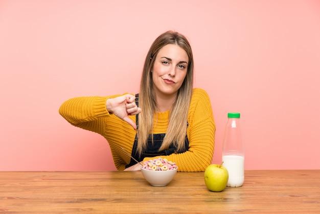 La giovane donna con la ciotola di cereali che mostra il pollice giù firma Foto Premium