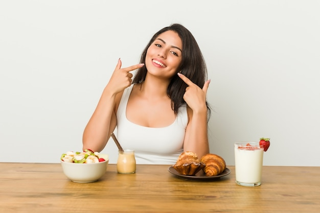 La giovane donna curvy che prende una prima colazione sorride, indicando le dita alla bocca. Foto Premium
