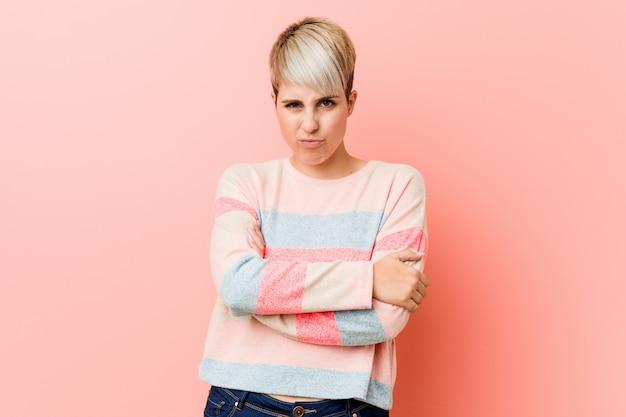 La giovane donna curvy naturale che aggrotta la fronte in disapprovazione, tiene le braccia piegate. Foto Premium