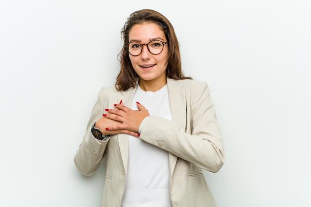La giovane donna d'affari europea ha un'espressione amichevole, premendo il palmo sul petto. concetto di amore. Foto Premium