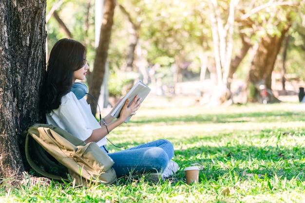La giovane donna degli studenti si rilassa e leggendo un libro che si siede sull'erba in parco Foto Premium