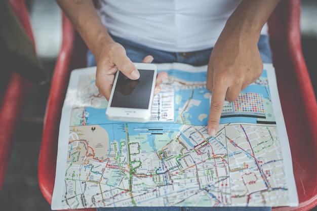 La giovane donna dei viaggiatori con lo zaino che guarda tiene una mappa alla stazione ferroviaria. giorno del turismo Foto Premium