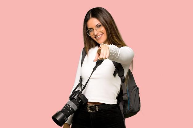 La giovane donna del fotografo indica il dito con un'espressione sicura sulla parete rosa isolata Foto Premium