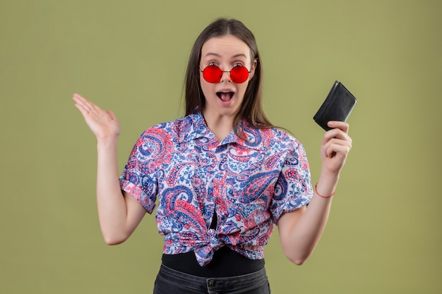 La giovane donna del viaggiatore che indossa gli occhiali da sole rossi che tengono il portafoglio che sembra stupito e sorpreso con le armi si è alzata sopra la parete verde Foto Gratuite