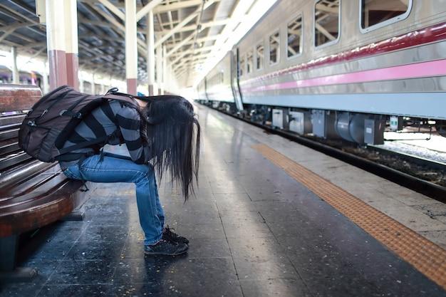 La giovane donna del viaggiatore con lo zaino ha depresso e sollecitato mentre aspettava il treno Foto Premium