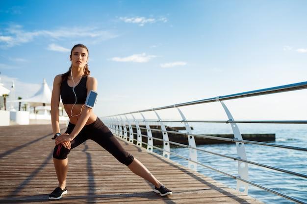La giovane donna di forma fisica che fa gli esercizi di sport con la costa di mare dietro Foto Gratuite