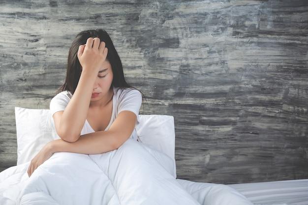La giovane donna è depressa su un letto bianco Foto Gratuite