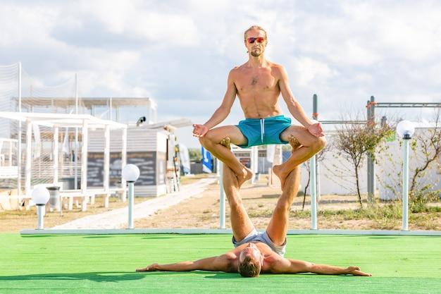 La giovane donna e gli uomini delle coppie sul campo che fa l'yoga di forma fisica si esercitano insieme. elemento acroyoga per forza ed equilibrio Foto Premium