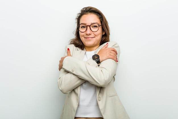 La giovane donna europea si abbraccia, sorride spensierata e felice. Foto Premium