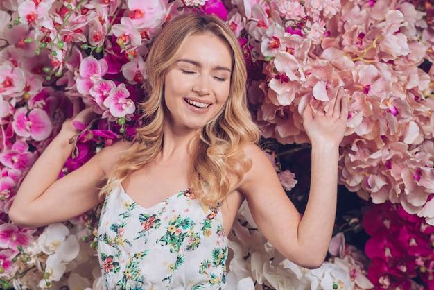 La giovane donna felice che si rilassa con i rami di un'orchidea fiorisce Foto Gratuite