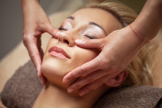 La giovane donna gode del massaggio facciale in stazione termale Foto Gratuite