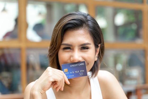 La giovane donna graziosa allegra ha usato la carta del cradit Foto Gratuite