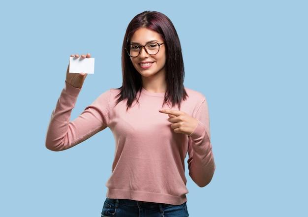 La giovane donna graziosa che sorride sicuro, offrendo un biglietto da visita, ha un'attività fiorente Foto Premium