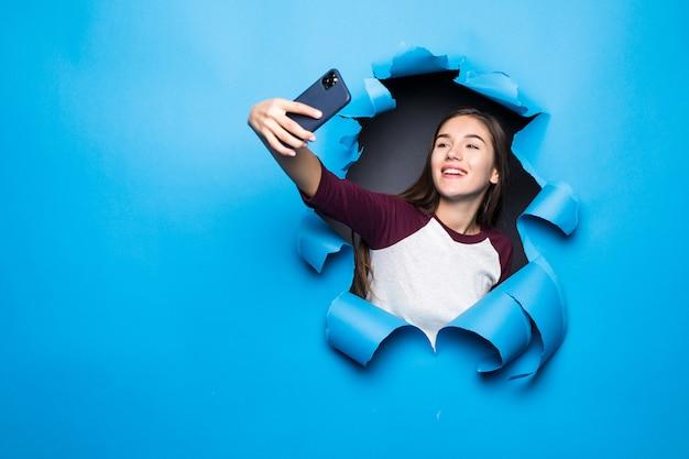 La giovane donna graziosa prende il selfie sul telefono mentre guarda attraverso il foro blu in parete di carta. Foto Gratuite