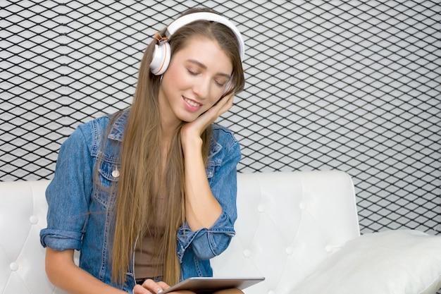 La giovane donna graziosa sta sedendosi sul sofà e sta indossando la cuffia per ascoltare la musica dalla compressa Foto Premium