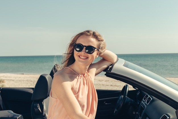 La giovane donna guida un'automobile sulla spiaggia Foto Premium