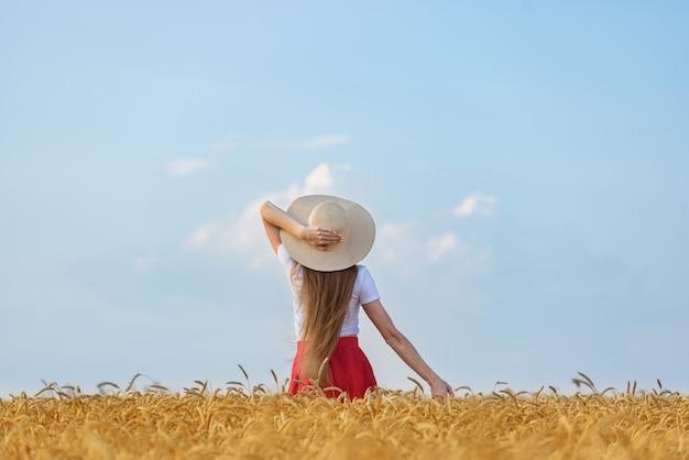 La giovane donna in cappello sta nel campo di frumento sul fondo del cielo blu. weekend all'aperto Foto Premium