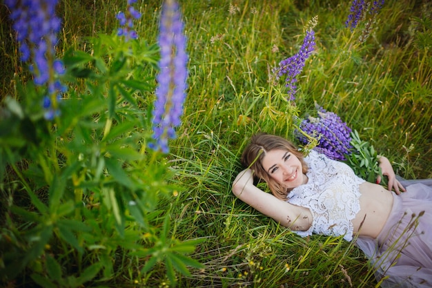 La giovane donna in vestito ricco si trova con il mazzo dei fiori viola sul campo verde Foto Gratuite