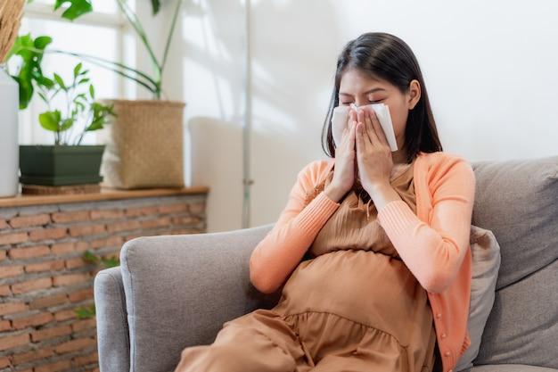 La giovane donna incinta asiatica soffre di influenza e starnuti, naso che cola, naso chiuso e poi soffiarsi il naso usando un fazzoletto Foto Premium