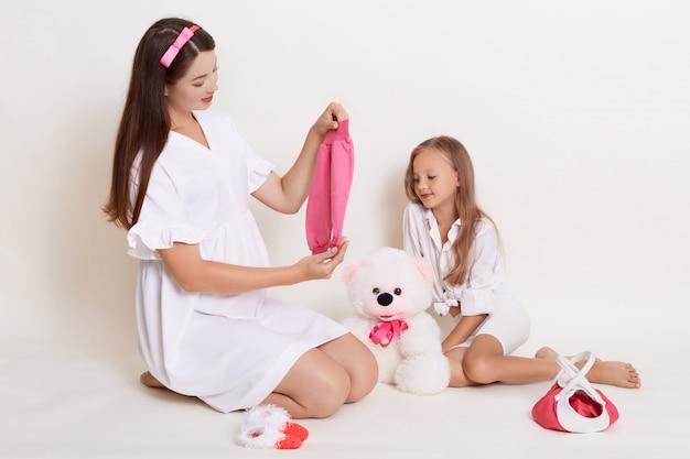 La giovane donna incinta sceglie i vestiti per il suo bambino Foto Gratuite