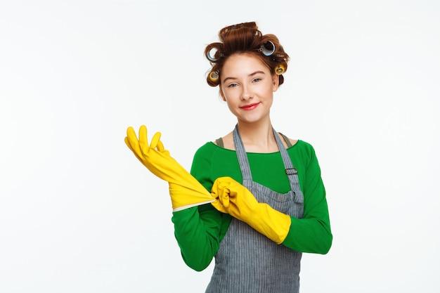 La giovane donna mette i guanti di gomma con i bigodini sui capelli Foto Gratuite