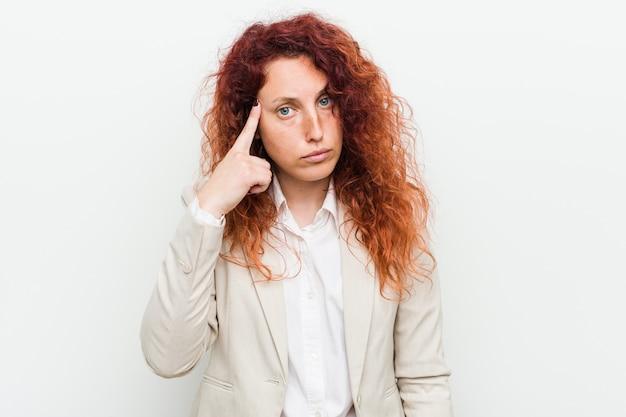 La giovane donna naturale di affari della testarossa che indica il tempio con il dito, pensando, si è concentrata su un compito Foto Premium