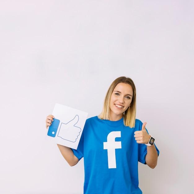 La giovane donna nella tenuta blu della maglietta gradisce l'icona che mostra il segno del thumbup Foto Gratuite