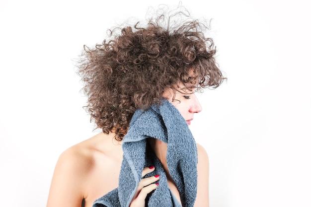 La giovane donna nuda con capelli ricci pulisce il suo ...