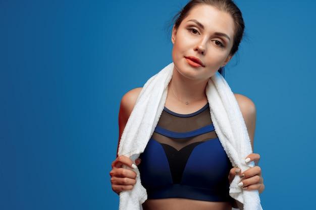 La giovane donna piacevole nello sport copre la tenuta dell'asciugamano in palestra Foto Premium