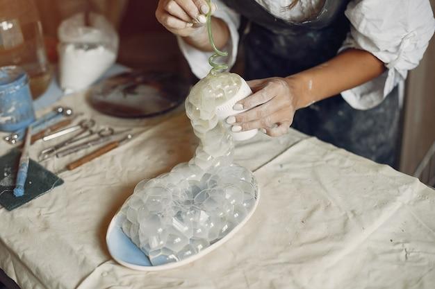 La giovane donna produce ceramiche in officina Foto Gratuite