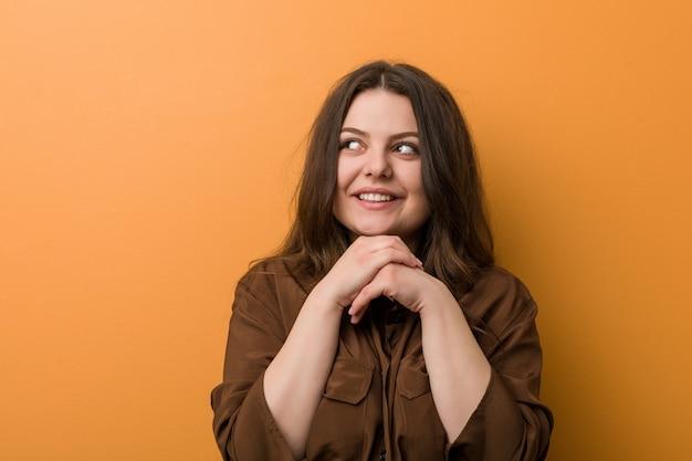 La giovane donna russa formosa tiene le mani sotto il mento, sta guardando felicemente da parte. Foto Premium
