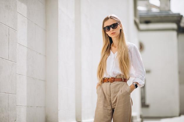 La giovane donna si è vestita in attrezzatura dell'estate fuori nella città Foto Gratuite