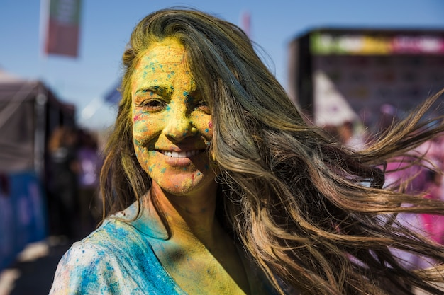 La giovane donna sorridente ha coperto il suo fronte di colore di holi che esamina la macchina fotografica Foto Gratuite