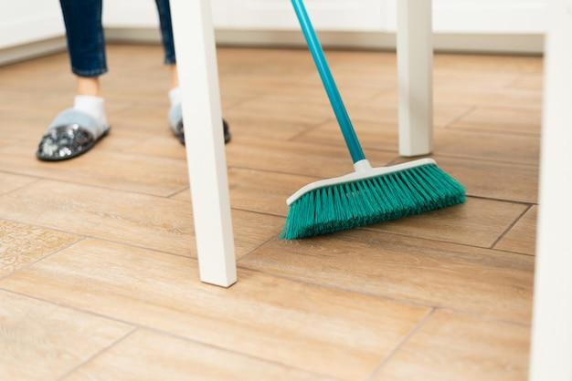 La giovane donna spazza la pavimentazione laminata in una cucina luminosa. la ragazza spazza polvere e sporco da sotto il tavolo bianco della cucina Foto Premium