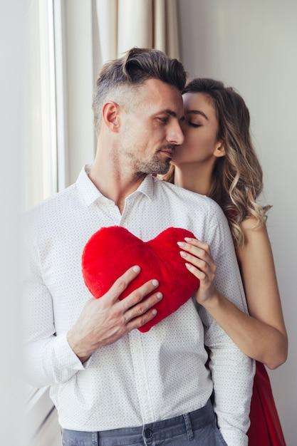 La giovane donna splendida in vestito rosso bacia il suo uomo e tiene il cuore del giocattolo della peluche Foto Gratuite